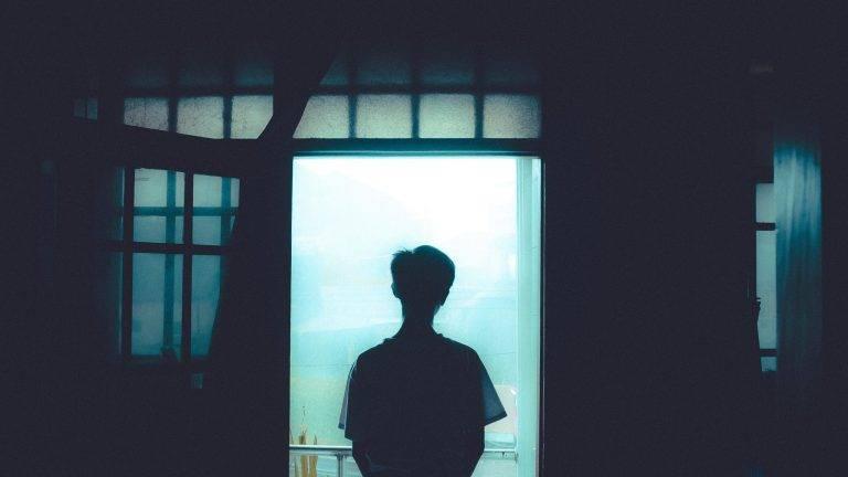 personne qui regarde par la fenêtre